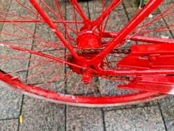 Selective focus close up view at a red bicycle wheel with metal spokes