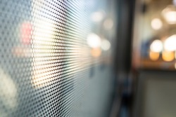 Selective focus, close-up view at One Way Vision sticker film with dot pattern on glass of Train's window and blurry background of train's passenger train and bokeh.