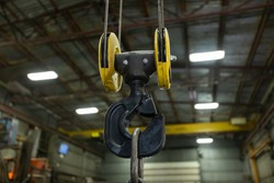 selective focus close up view of lifting hook with safety latch attached to sheaves suspended by wires ropes, factory or workshop interior background.