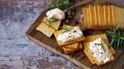 Selective focus. Crackers with cream cheese on a wooden board.
