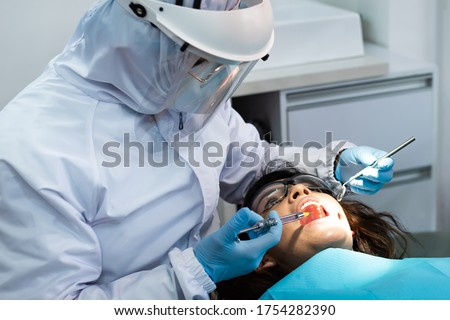 Selective focus. Dentist about to apply anesthesia to young female patient Foto stock ©