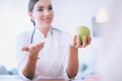 Selective focus. Female doctor holds apple and pills while discussing with patient in the office in hospital. High quality photo