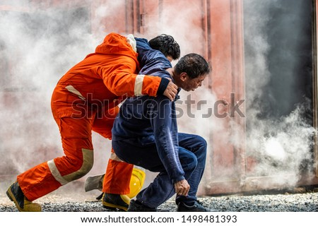 Selective focus firefighter in fire suit on safety rescue duty help a man suffocating smoke in burning premises by first aid emergency and carry him to outside. Safety, rescue and health care concept. Stock photo ©