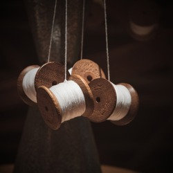 Selective focus foreground on hanging group of thread shabby bobbins with white cotton yarn on blurred dark brown background.Vintage wooden spools of white threads closeup.
