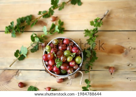 Selective focus. Fresh gooseberries in a bowl on a wooden surface. Gooseberry leaves. Gooseberry harvest. Stock photo ©