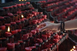 Selective focus hand putting red candle