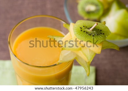 Selective focus image of a yellow smoothie with tropical fruits like kiwi, mango and star fruit.