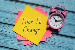 Selective focus image of colorful sticky note and clock with Time To Change wording over a wooden background.  Motivational concept.