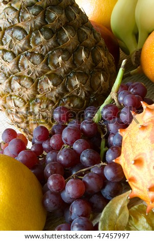 Selective focus image of different tropical fruits like horned melon, graves, passion fruit, banana, lemon and pineapple.