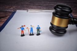 Selective focus image of gavel with miniature of labor. Labor law concept.