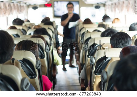 Selective focus image of Private bus with tourists and guided tour.