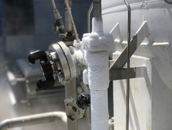 Selective focus Liquid nitrogen pipe and leakage or blowing from nitrogen tank at gas farm plant, Industrial concept.
