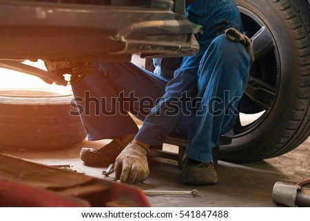 Selective focus low key  young man using tool  for repair brake car  a part of wheel tire in garage.