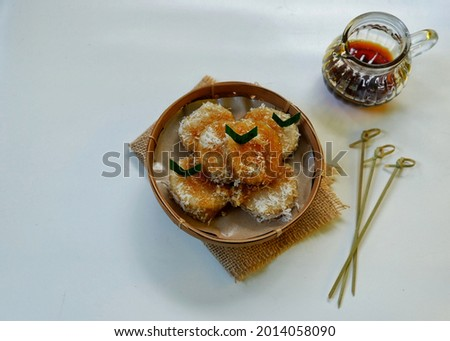 Selective focus Lupis, Indonesian Traditional Snack Made From Sticky Rice, Wrapped with banana Leaf, Served with Liquid Palm Sugar and Grated Coconut.  Zdjęcia stock ©