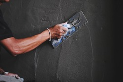 Selective focus, Man hand plastering a wall with trowel. Construction worker. Masonry tool. Construction industry concept.