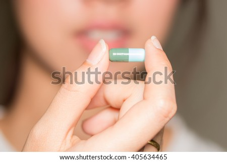 selective focus Medicine pills or capsules in hand, palm or fingers. Drug prescription for treatment medication. Woman, young female, person taking vitamin, painkiller, antibiotic #405634465