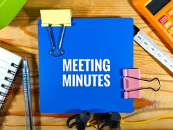 Selective focus.MEETING MINUTES in white word with paper clips, notebook, calculator,earphone and measuring tape with wooden background.Business and education concept.