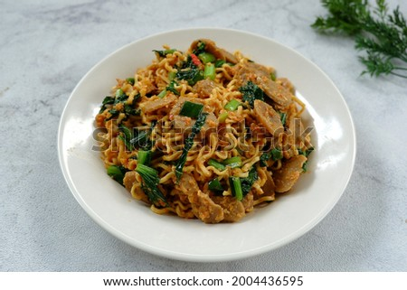 Selective focus Mie Goreng Tek-tek or fried noodles with topping slice meatballs, eggs and mustard greens (caisim or sawi hijau). Served in white plate. Look like noised with fried noodles.  Stok fotoğraf ©