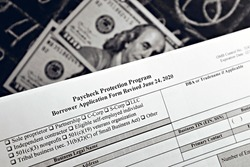 selective focus monochrome photo of paycheck protection program borrower application form revised, on a background of dollar bills and a chalk board with numbers