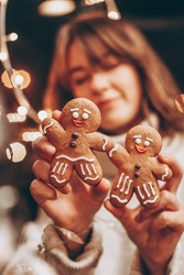 selective focus, noise effect: Merry Christmas and Happy New Year! Christmas cookies, gingerbread man figure holding a smiling woman in her hands
