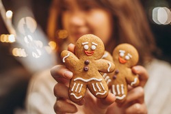 selective focus, noise effect: Merry Christmas and Happy New Year Christmas cookies, gingerbread man figure holding a smiling woman in her hands. copy space