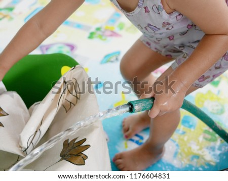 Selective focus of a baby little hand holding water hose to fill water into a bucket while washing cloth at home - child development through doing housework #1176604831