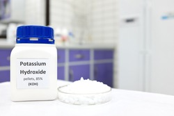 Selective focus of a bottle of pure potassium hydroxide or KOH chemical compound beside a petri dish with white solid pellets. Chemistry research laboratory background with copy space.