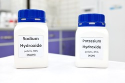 Selective focus of a bottle of pure sodium hydroxide and potassium hydroxide chemical compound. Chemistry research laboratory background with copy space.