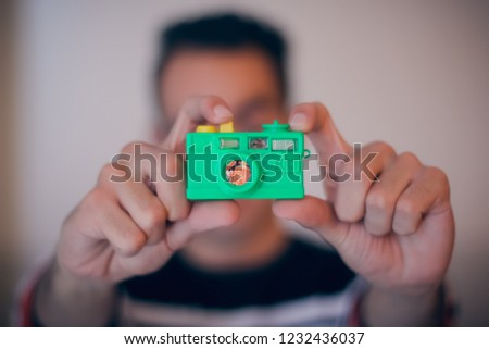 Selective focus of a boy taking photo of his toy camera.