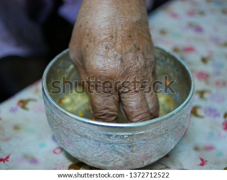 Selective focus of a hand of elderly person dipping into a cup ( salung ) filled with holy turmeric water before spraying the blessing water during Rod Nam Dam Hua ceremony, paying respect to elders