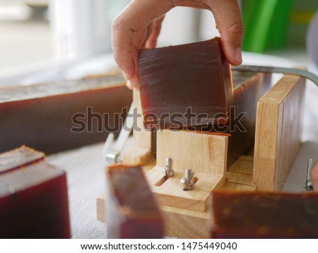 Selective focus of a hand picking up a bar / piece of homemade soap after the loaf of soap was cut by a single wire soap cutter