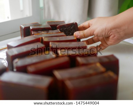 Selective focus of a hand picking up homemade bars / pieces of soap - soap making