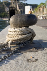 Selective focus of a Old rope And a Chain tied tight in a nautical bollard in the harbour With a blurry background with the boardwalk