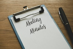 Selective focus of a pen and clipboard with paper written with Meeting Minutes on wooden background.