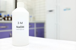 Selective focus of a plastic bottle of sodium hydroxide solution or NaOH chemical reagent. Chemistry research laboratory background with copy space.