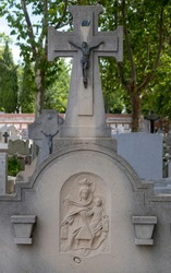 selective focus of a tombstone of a Catholic burial with a cross and a bronze sculpture of Christ and a relief of the Virgin of Carmen worn by time under the shade of some trees
