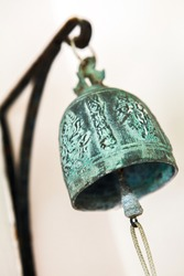 selective focus of a weathered brass metal door bell ringer with green-blue oxidation known as the patina effect.