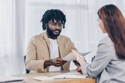 Selective focus of african american employee giving papers to recruiter at job interview in office