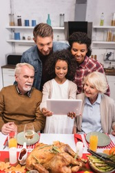 Selective focus of african american girl holding digital tablet near family during thanksgiving celebration