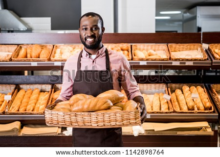 selective focus of african american male shop assistant in apron with loaves of bread in supermarket