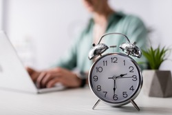 Selective focus of alarm clock on table near man using laptop at home, concept of time management