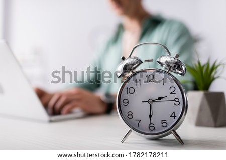 Selective focus of alarm clock on table near man using laptop at home, concept of time management Foto stock ©