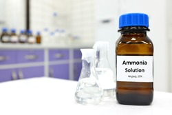 Selective focus of ammonia solution or ammonium hydroxide in glass amber bottle inside a chemistry laboratory with copy space.