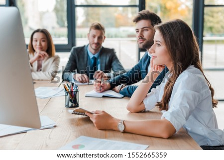 selective focus of attractive businesswoman looking at computer during webinar monitor near multicultural coworkers in office
