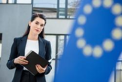 selective focus of attractive diplomat holding folder near european union flag
