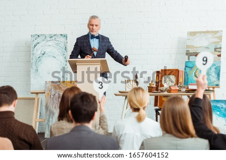 selective focus of auctioneer holding gavel and microphone and looking at buyers during auction Stock foto ©