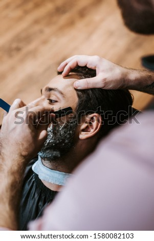 selective focus of barber shaving man with shaving cream on face
