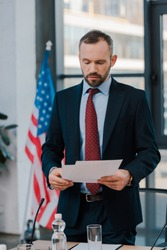 selective focus of bearded diplomat in suit holding papers near american flag