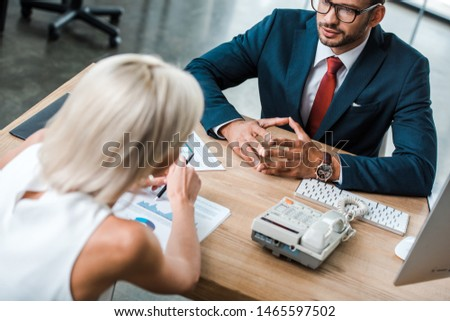 selective focus of bearded man in glasses looking at blonde coworker in office