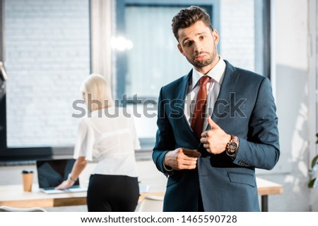 selective focus of bearded upset businessman showing thumb up near coworker in office